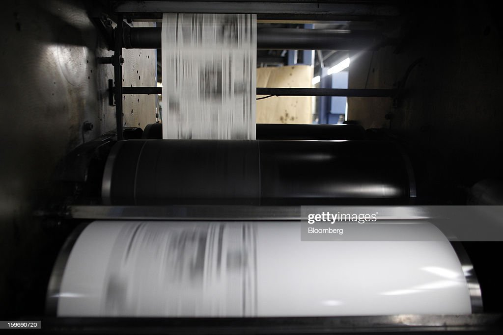 Printed pages run through the presses at the Kathimerini printing plant in Paiania, Greece, on Thursday, Jan. 17, 2013. An anarchist group claimed responsibility for a series of attacks early on Jan. 11 when unidentified perpetrators threw makeshift bombs made from propane gas canisters into the homes of five Greek journalists working for national media saying it was to protest coverage of the country's financial crisis seen as sympathetic to the government. Photographer: Kostas Tsironis/Bloomberg via Getty Images