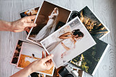 Printed wedding photos with the bride and groom, a vintage black camera and woman hands with two photos. Cropped image
