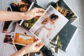 Printed wedding photos with the bride and groom, a vintage black camera, open photoalbum and woman hands with photo
