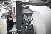 Printer adjusting paper feed on press in printworks