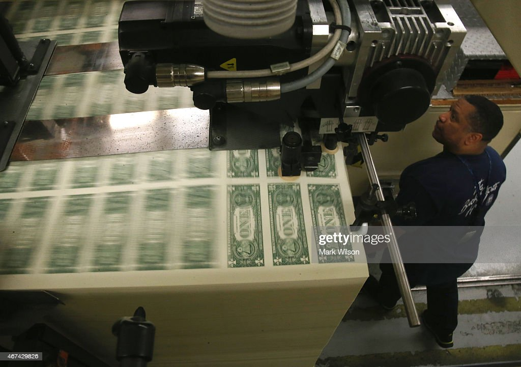 Printer Eugene Turner runs a press that is printing one dollar bills at the Bureau of Engraving and Printing on March 24 2015 in Washington DC The...