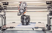 3D printer printing a model in the form of black skull close-up. The 4ht industrial revolution. Automatic three dimensional performs plastic modeling. Progressive modern additive technology