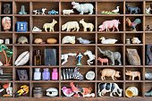 A collection of found objects including toy farm and zoo animals, old cars, seashells, bottles, Cupid dolls,