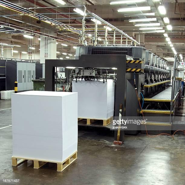 Druckmaschine mit Haufen Zeitungen in Druck-Fabrik