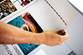 man's hand checking color proofs for printing, during production