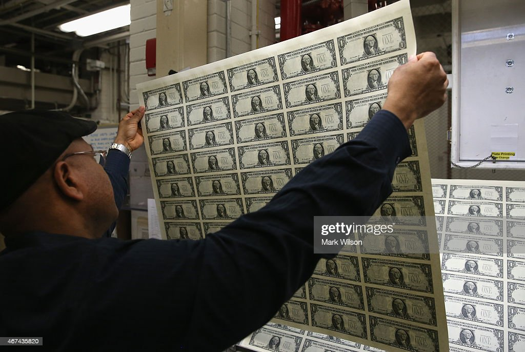 Printing Supervisor Donavan Elliott inspects newly printed sheets of one dollar bills at the Bureau of Engraving and Printing on March 24 2015 in...