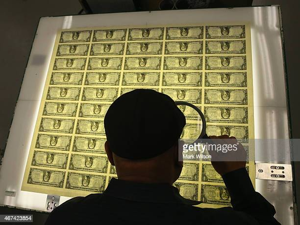 Printing Supervisor Donavan Elliott inspects sheets of one dollar bills run through the printing press at the Bureau of Engraving and Printing on...