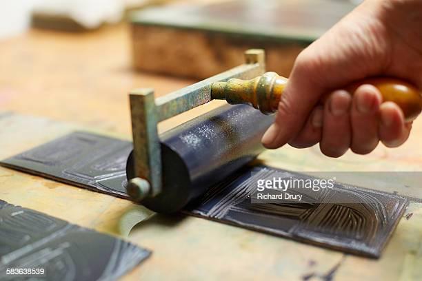 Printmaker inking lino print block