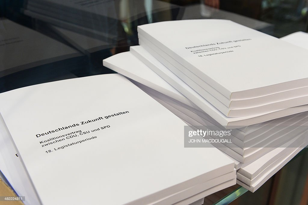 Prints of the agreement to form a coalition government to be signed by Christian Democratic Party (CDU), Bavarian allies Christian Social Union (CSU) and Social Democratic Party (SPD) lie on a table on November 27, 2013 in Berlin before their press conference. German Chancellor Merkel agreed earlier in the morning to form a coalition government with campaign rivals the Social Democrats, two months after her conservatives won elections but fell short of a full majority. MACDOUGALL