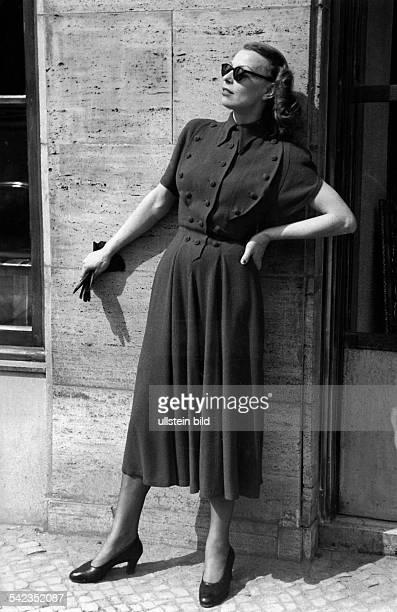 Prinzesskleid aus roter Wolle mit einemaparten Ärmelschnitt und reichem Knopfschmuck Unterhalb der Taille münden diePrinzessnähte in tiefen...