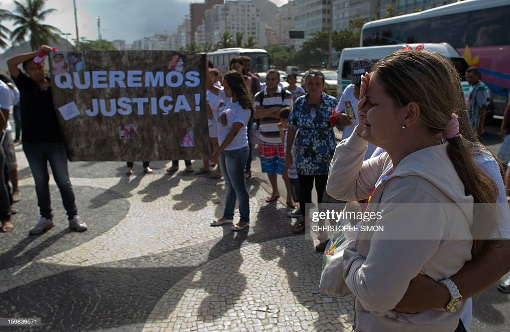 Priscilia (R), 27, whose daughter Geovanna Vitoria de Barros, 1, was shot dead last Friday 18 during a robbery attack to their car in Baixo Fluminense, cries during a demonstration on Copacabana beach in Rio de Janeiro on January 21, 2013.