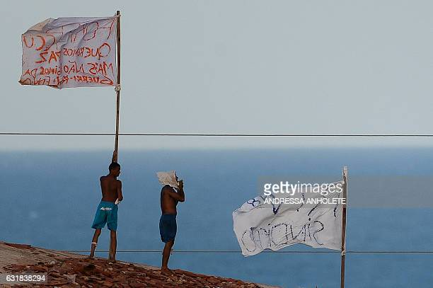 TOPSHOT Prisioners atop the roof of the compound celebrate the transfer of their leaders after a negotiation with the police at the Alcacuz...