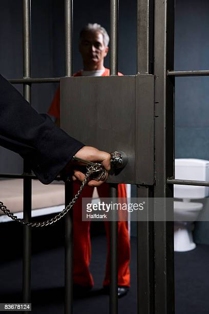 A prison guard locking a prison cell door