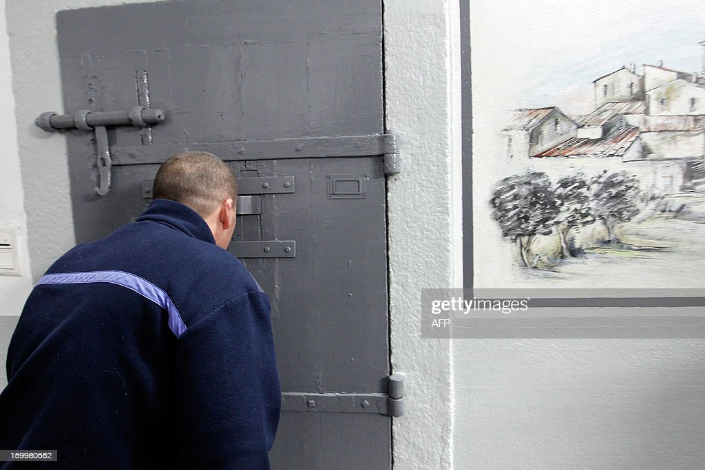 A prison guard looks into a cell at the Ajaccio's jail on January 24, 2013, in Ajaccio, Corsica. AFP PHOTO / PASCAL POCHARD-CASABIANCA