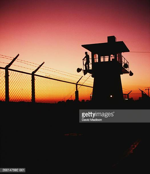 Prison guard on duty in security tower at sunset, silhouette