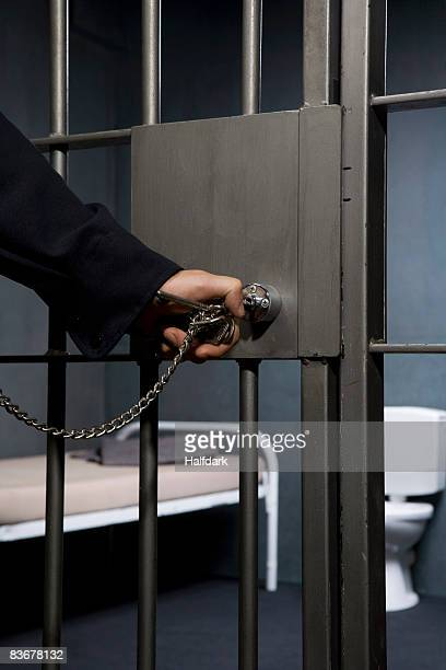 A prison guard unlocking a prison cell door