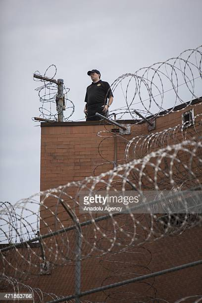 A prison guard watches from the roof top of the prison as approximately two thousand people gather to march through the streets after it was...