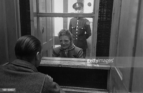 Prison officer Davidson watches as a prisoner talks to a visitor at Strangeways Prison in Manchester November 1948 Original publication Picture Post...