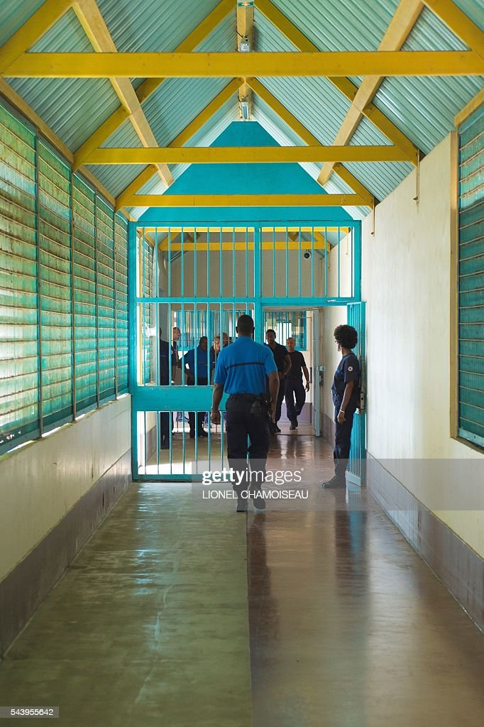 A prison warden walks through a hallway on June 30, 2016 during the inauguration of the extension of the Ducos prison in Ducos, near Fort-de-france, on the Caribbean island of Martinique. / AFP / Lionel CHAMOISEAU
