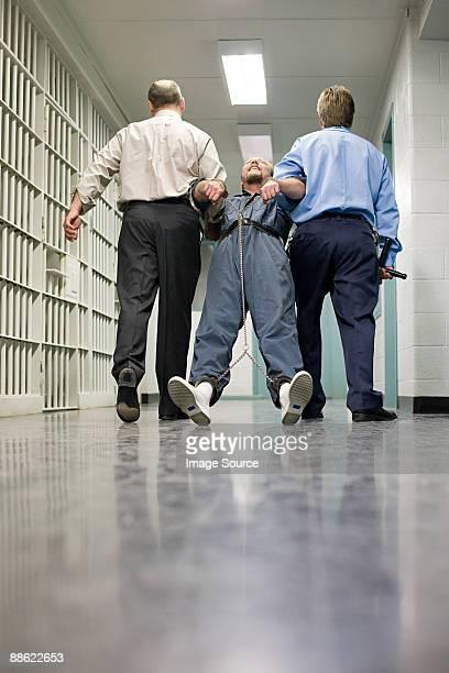 Prisoner being dragged down corridor
