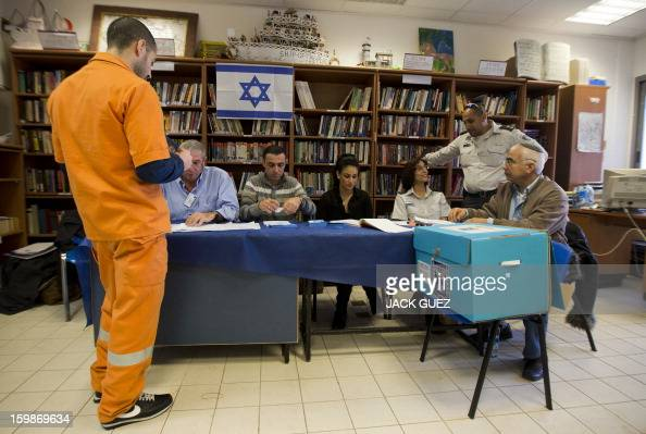 A prisoner has his name checked on a register as he waits to cast his ballot on January 22 at a polling station in the Hasharon prison in Hadarim...