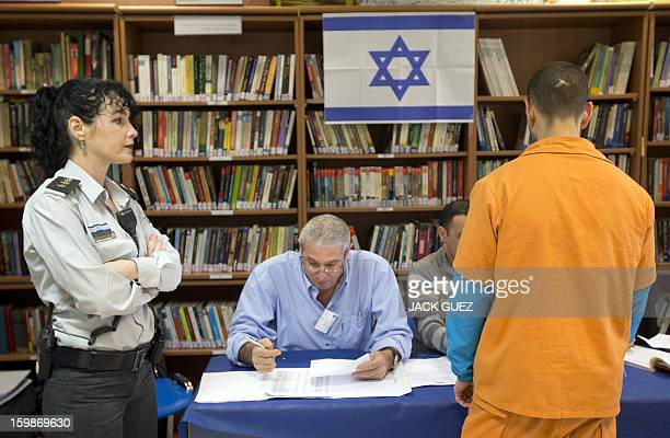 A prisoner has his name checked on a vote register as he waits to cast his ballot on January 22 at a polling station in the Hasharon prison in...