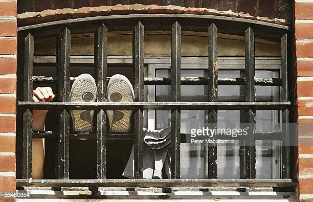 A prisoner holds his hand up at the window of a cell at Norwich Prison on August 25 2005 in Norwich England A Chief Inspector of Prisons report on...