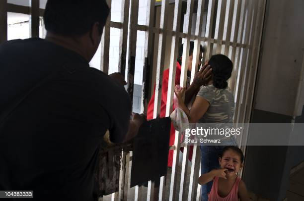 A prisoner kisses his wife goodbye as their young girl cries before masked security police transfer the new inmate in to his cell in the prison of...