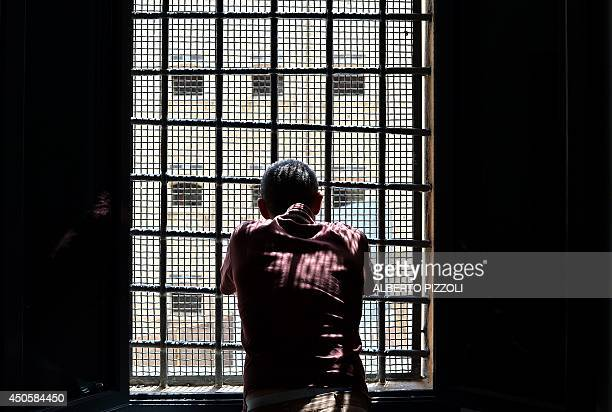 A prisoner looks out a window at Regina Coeli prison in Rome on May 30 2014 Crouched on bunk beds in the narrow cells of the Regina Coeli lockup in...