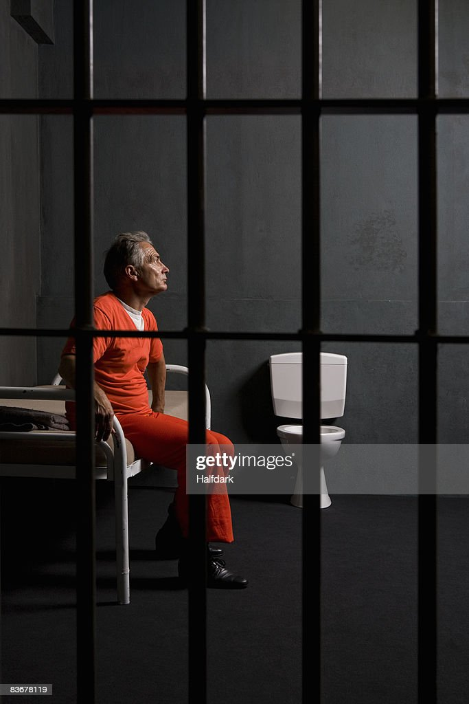 A prisoner sitting in his prison cell : Stock Photo