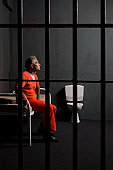 A prisoner sitting in his prison cell