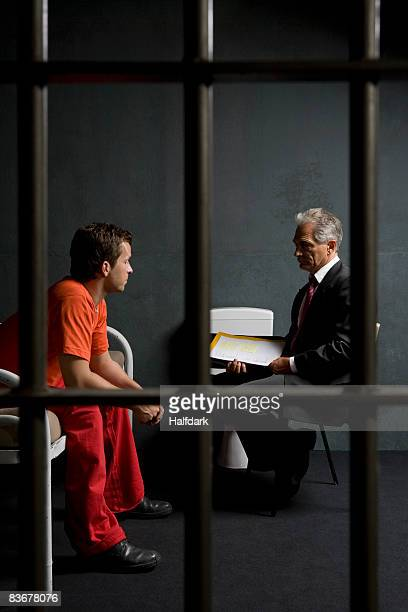 A prisoner talking to a lawyer in a prison cell