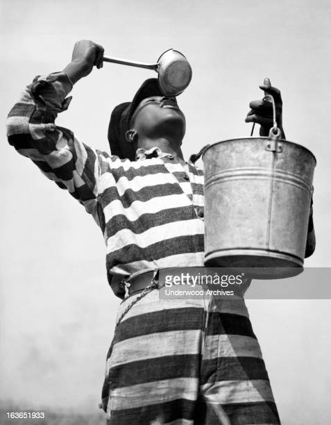 A prisoner working on the Bibb County chain gang quenches his thirst after hours of toil on a road Macon Georgia March 8 1937