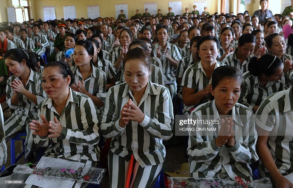 Prisoners applaud after listening to a presidential amnesty decision during a ceremony at the Hoang Tien prison in Chi Linh district, northern province of Hai Duong on August 30, 2013. Vietnam will free more than 15,000 convicts to mark its independence day celebrations, the president's office said on August 29, in a major amnesty that excludes prominent political prisoners. AFP PHOTO/HOANG DINH Nam