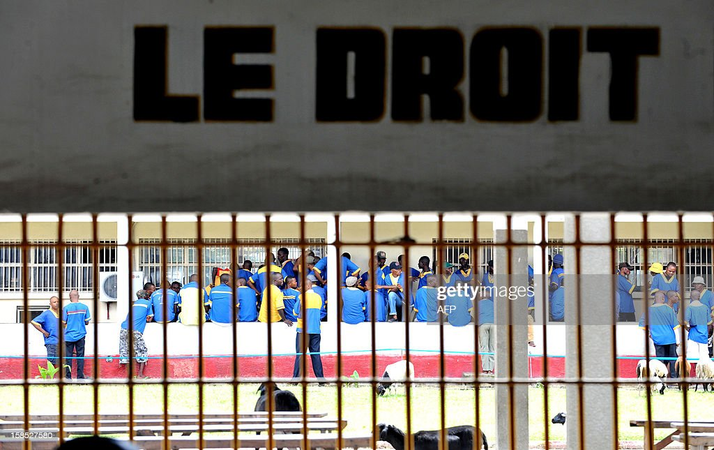 Prisoners are seen at the Makala prison in Kinshasa on December 18, 2012 from behind the bars of the windows of a court room. AFP PHOTO / JUNIOR D. KANNAH