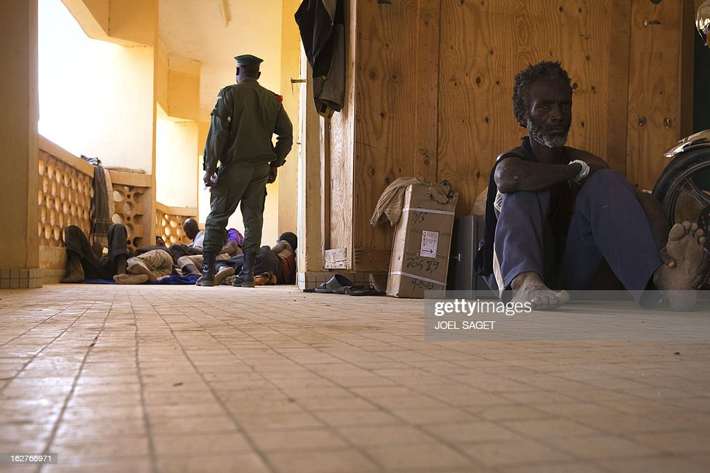 Prisoners are watched in a jail at the gendarmerie in the northern Malian city of Gao on February 26, 2013. French and Malian government forces reconquered on January 26 the city opf Gao, two weeks after Paris launched an offensive in the north. AFP PHOTO /JOEL SAGET