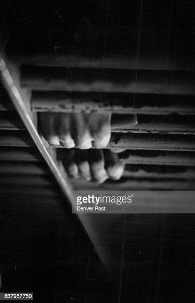Prisoner's clenched hands around bars of cell reflect one of the many moods of the Denver City Jail on the fourth floor Denver Police Department...