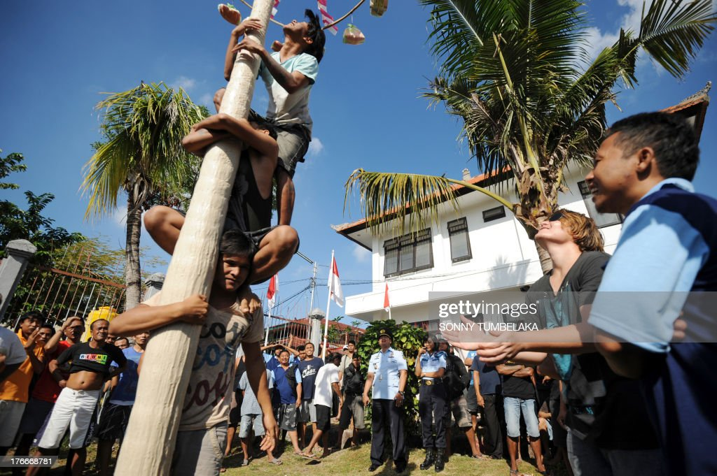 Prisoners climb a pole as they participate in official ceremonies and games marking Indonesia's 68th Independence Day at Kerobokan prison in Denpasar on Indonesia's resort island of Bali on August 17, 2013. Indonesia officials annually offer remissions to some prison sentences on the country's Independence Day for good behaviour. Bali's notorious Kerobokan prison is well known as the place holding several foreign inmates held for high-profile drugs offences. AFP PHOTO / SONNY TUMBELAKA