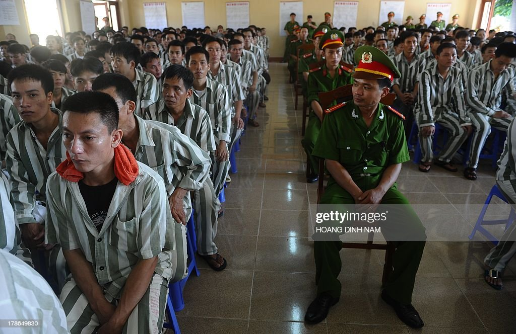 Prisoners listen to a presidential amnesty decision during a ceremony at the Hoang Tien prison in Chi Linh district, northern province of Hai Duong on August 30, 2013. Vietnam will free more than 15,000 convicts to mark its independence day celebrations, the president's office said on August 29, in a major amnesty that excludes prominent political prisoners. AFP PHOTO/HOANG DINH Nam