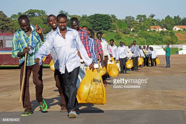 Prisoners of war from the forces of the Sudanese ruling National Congress Party walk towards an Ethiopian airplane on March 5 in Entebbe to be taken...