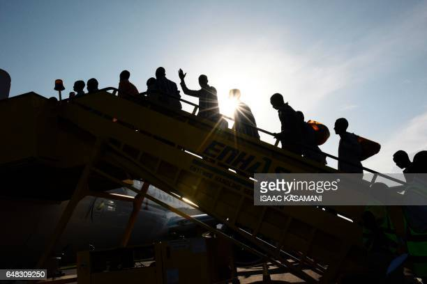 TOPSHOT Prisoners of war from the ruling Sudan's National Congress Party board an airplane to travel home after they being released by the Sudan...