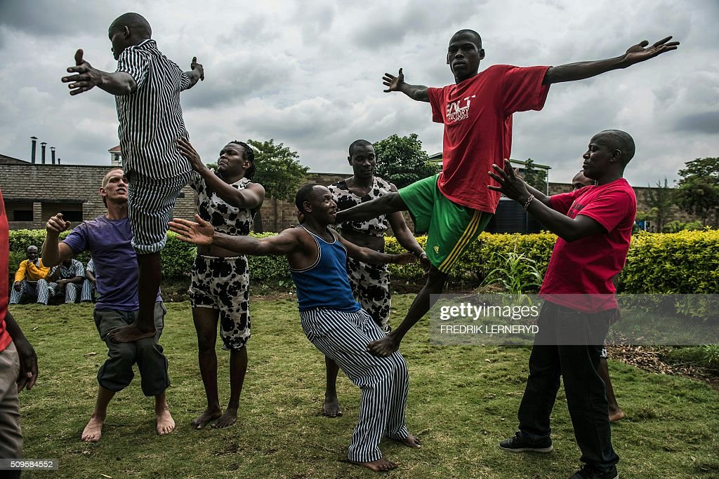 Prisoners try some acrobatic figures during a workshop with the Sarakasi circus performers at Kamiti prison, Nairobi February 11, 2016. Sarakasi Circus performes dance, acrobatics and workshops for the inmates at Kamiti maximum security prison in order provide another form of engagement during their incarceration. / AFP / FREDRIK LERNERYD