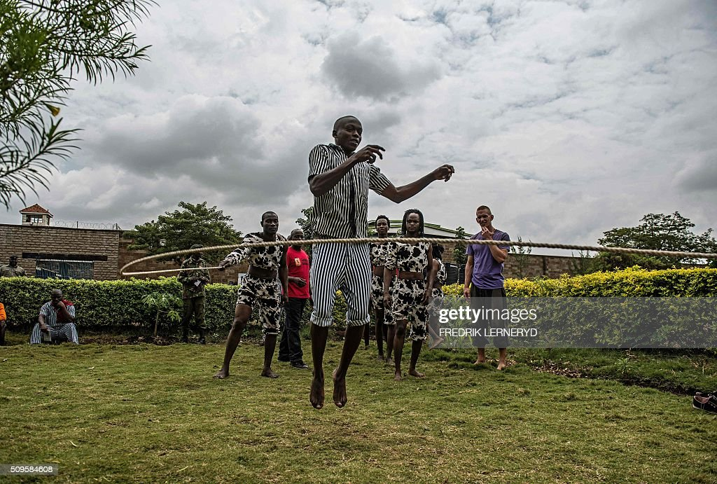 Prisoners try some acrobatic moves during a workshop with the Sarakasi circus performers at Kamiti prison, Nairobi February 11, 2016. Sarakasi Circus performes dance, acrobatics and workshops for the inmates at Kamiti maximum security prison in order provide another form of engagement during their incarceration. / AFP / FREDRIK LERNERYD