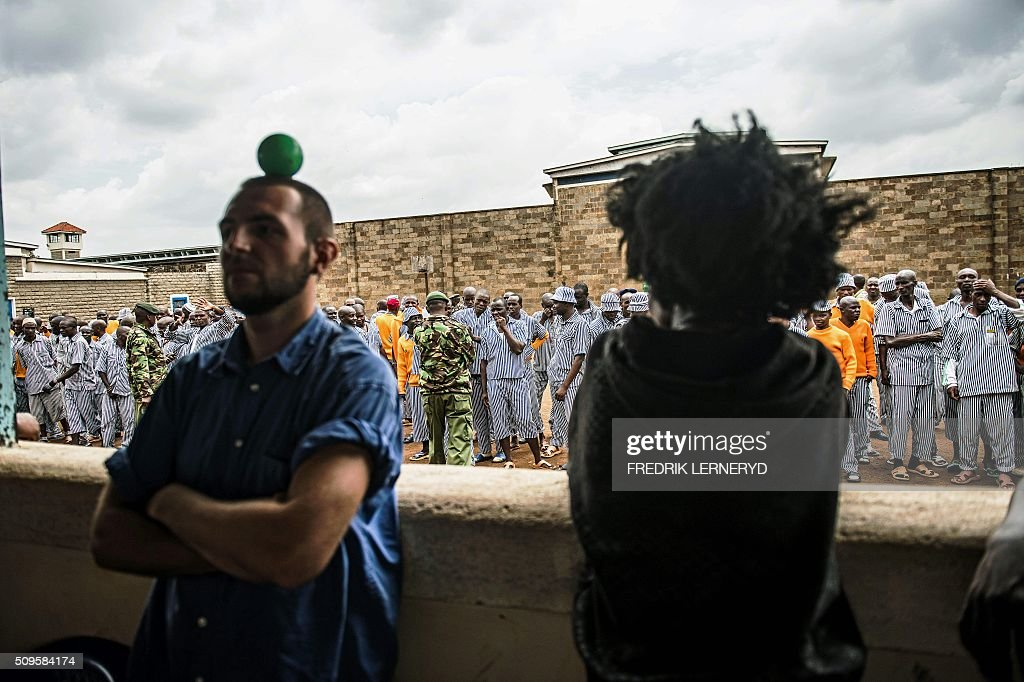 Prisoners wait and line up to watch the Sarakasi circus perform for them at Kamiti prison, in Nairobi on February 11, 2016. Sarakasi Circus performes dance, acrobatics and workshops for the inmates at Kamiti maximum security prison in order provide another form of engagement during their incarceration. / AFP / FREDRIK LERNERYD