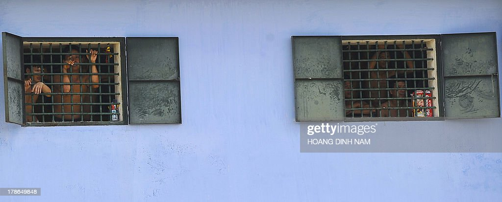Prisoners watch from windows as released prisoners leave the Hoang Tien prison in Chi Linh district, northern province of Hai Duong on August 30, 2013. Vietnam will free more than 15,000 convicts to mark its independence day celebrations, the president's office said on August 29, in a major amnesty that excludes prominent political prisoners. AFP PHOTO/HOANG DINH Nam