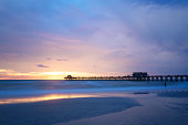 The sun goes down at the Naples Pier in the Gulf of Mexico, Southwest Florida, USA. Amazing spot of the sun coming down at blue hour in this idyllic place for family vacation and relax.