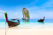 Pristine beach with traditional Thai longtail boats on turquoise transparent Andaman sea water on Poda island near Krabi, Koh Phiphi and Phuket, Thailand, vacation travel destination