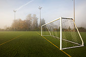 A pristine sport turf field and white post soccer goal viewed in autumn fog and morning light.