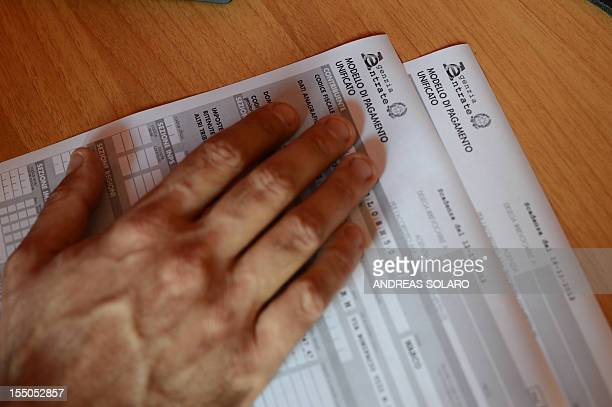 A private business consultant looks at an official tax form on October 22 2012 in Rome AFP PHOTO / ANDREAS SOLARO