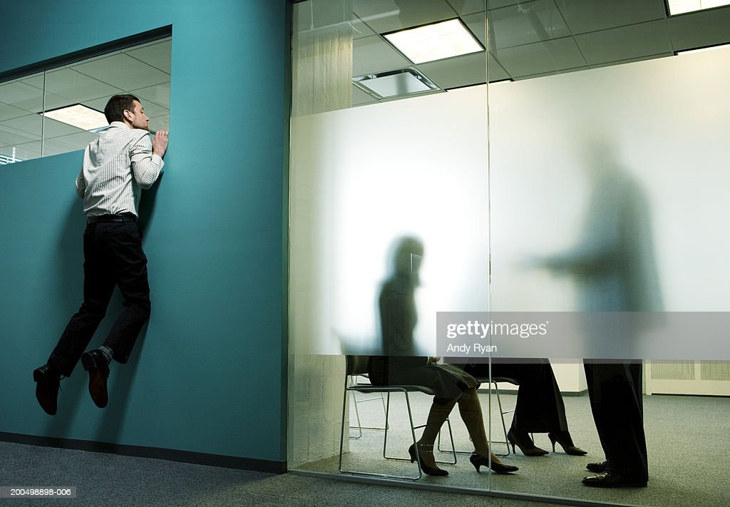 Private business meeting behind frosted glass in office, man spying : Stock Photo